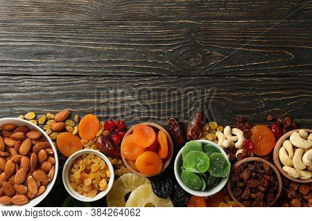 Bowls With Dried Fruits And Nuts On Wooden Background