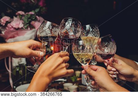 Close Up Shot Of Group Of People Clinking Glasses With Wine Or Champagne In Front Of Bokeh Backgroun