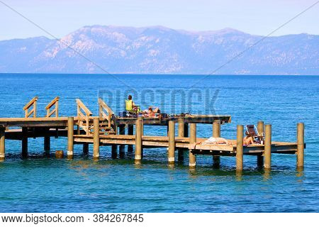 September 3, 2020 In Lake Tahoe, Ca:  Wooden Docks With People Sunbathing And Swimming On A Lake Wit