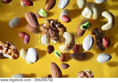 Nuts In The Air On A Yellow Background, Flying Nuts. Healthy Brain Food, Diet, Protein, Almonds, Wal