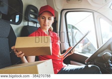 Female Delivery Service Worker In Red Uniform Sitting In Van And Working With Packages