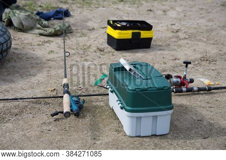Fishing On The Sandy Beach. Fishing Rods And A Box With Baubles And Other Fishing Accessories On The