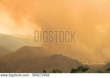 Wildfire Burning On The Arid Foothills Of The Sierra Nevada Mountains, Ca With Smoke Lifting Into Th