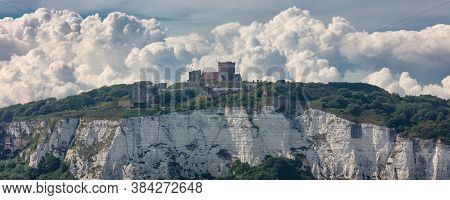 Panoramic Shot Of The White Cliffs Of Dover And A Castle On Top Of The Cliff. Beautiful Fluffy Cloud