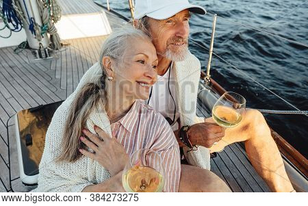 Senior Couple Wrapped With Plaid And Sitting On A Yacht Deck With Bocals Of Wine. Two Loving Mature
