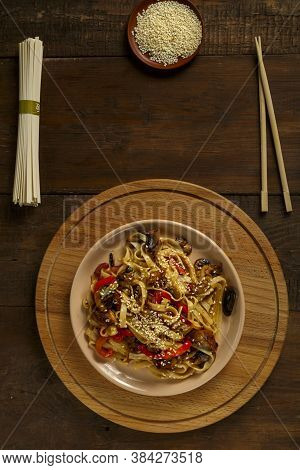 Udon With Chicken And Mushrooms In Pad Thai Sauce On A Plate Next To Sesame And Udon.