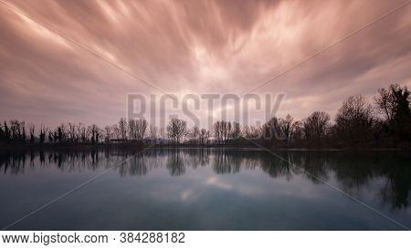 A Red And Cloudy Sky Reflected In The Water Of A Lake At Sunset Time, Natural Landscape