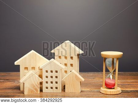 Wooden Figures Of Houses And Sand Hourglass. Mortgage And Loan Concept. Temporary Rental Housing And