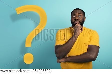 Confused And Pensive Expression Of A Boy With Many Questions . Cyan Colored Background