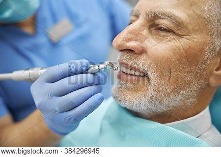 Elderly Man Smiling While Having His Teeth Polished