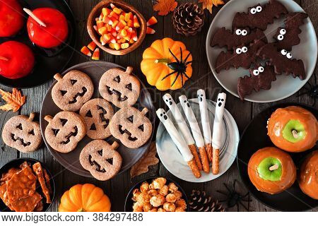 Halloween Treat Table Scene Over A Rustic Dark Wood Background. Above View. Assortment Of Candied Ap