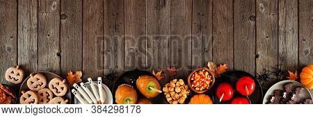 Rustic Halloween Treat Bottom Border Over A Dark Wood Banner Background With Copy Space. Above View.