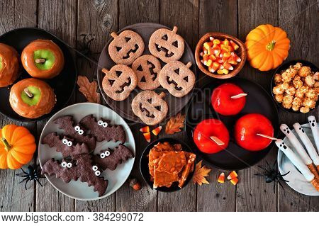 Rustic Halloween Treat Table Scene Over A Dark Wood Background. Top View. Variety Of Candied Apples,