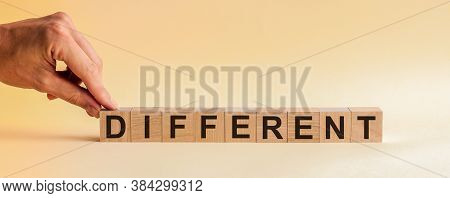 Different Message Word On A Wooden Desk On Cube Blocks. The Hand Puts A Wooden Cube With The Letter