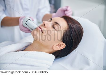 Beautiful Lady With Eyes Closed Undergoing A Cosmetic Procedure
