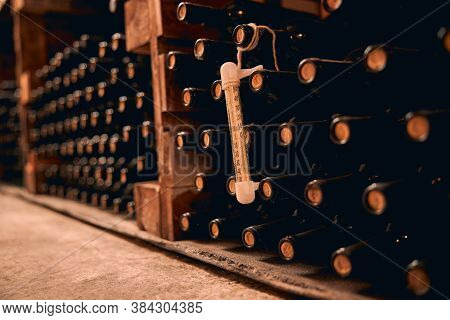 Wine Bottles With Thermometer Stored In Wine Cellar