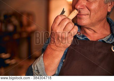 Male Winemaker Enjoying The Scent Of Wine Cork