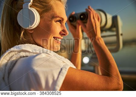 Joyful Woman In Headphones Using Observation Binoculars On The Street