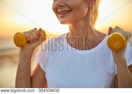 Joyous Suntanned Sportswoman With Dumbbells Standing Outside