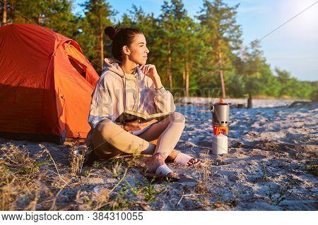 Charming Female Traveler Reading Book On The Beach