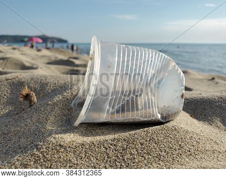 Disposable Plastic Glass Discarded On Sandy Sea Coast Ecosystem, Nature Pollution
