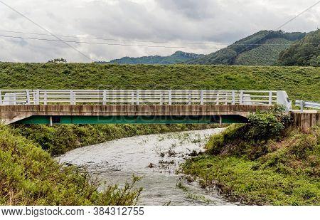 Rural Concrete Bridge Over Small Stream Under Cloudy Overcast Sky.