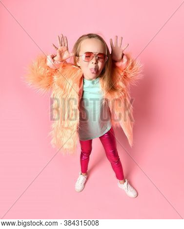 Trendy Little Girl In Pink Glasses, Blue Shirt, Glossy Leggings And Fluffy Coat Teasing Someone Loll