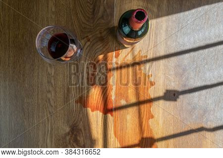 Top View Of Glass And Bottle Of Red Wine With Spilled Wine On The Table