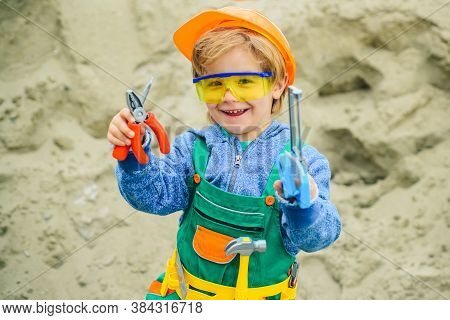 Cute Little Boy In Yellow Hard Hat And Tool Belt Smiling At Camera Isolated On Grey.