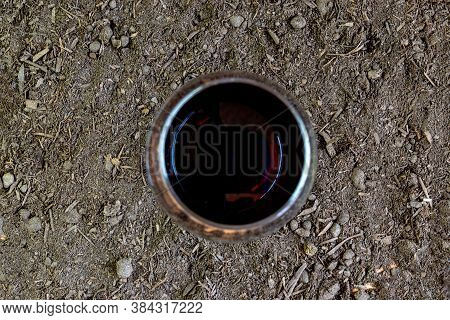 Top View Of Red Wine Glass On Fertile Land