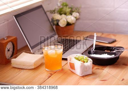Eat Sandwich And Meal Plastic Box With Orange Juice. During Work With Laptop Computer. Work And Eat