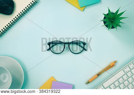 Glasses At Center And Office Supplies As Keyboard Pen Stick Note Office Plants Spiral Notebook Mouse
