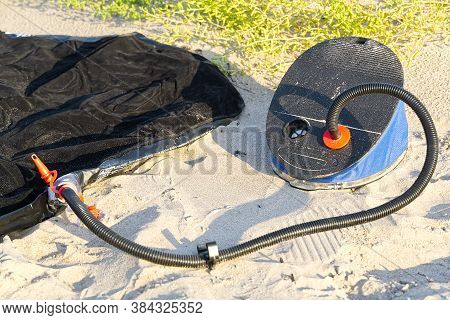 Foot Pump Near Inflatable Mattress Or Air Bed At Sandy Beach. Inflates Air Mattress With Foot Pump O
