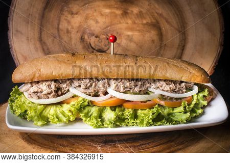 Tuna Baguette With Onion Tomato And Letuce On A Wood Background