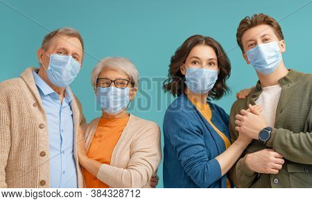 Family is wearing facemasks during coronavirus and flu outbreak. Virus and illness protection, quarantine. COVID-2019. Taking on or taking off masks. People on blue wall background.