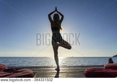 Silhouette Of Woman Standing At Yoga Pose On The Tropical Beach During Sunset. Caucasian Girl Practi
