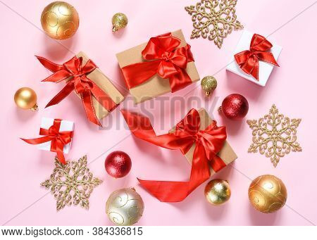 Beautiful Composition. Christmas Pink Background With Fir, Christmas Gifts And Decor. Top View With
