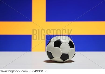 Small Football On The White Floor With Out Focus Blue And Yelow Color Of Swedish Nation Flag Backgro