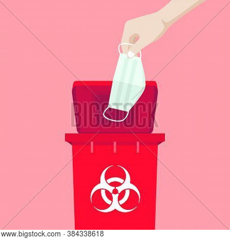 Hand Holding A Mask Is Above The Red Bin, With The Symbol Of Infectious Waste. How To Discard The Su