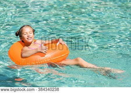 Pleased Girl Showing Thumb Up While Floating In Pool On Swin Ring With Closed Eyes