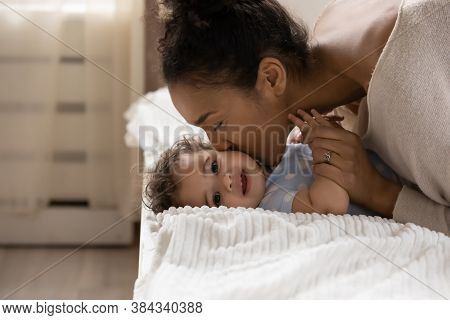 Affectionate African Ethnicity Mother Kissing Cheek Of Little Toddler Baby.