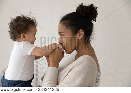Young African Ethnicity Woman Kissing Cute Little Hands Of Baby.