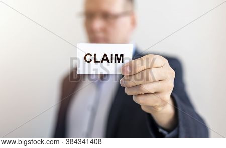 Businessman Holding A Paper Card With Text Claim In Hand, Lawsuit And Claim Concept