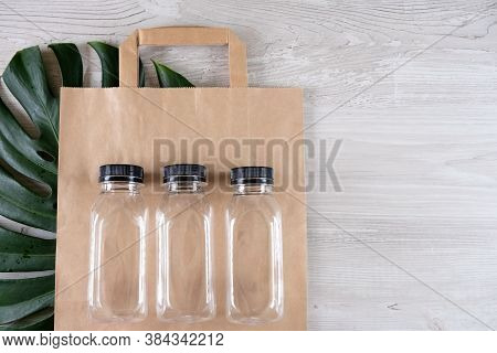 Three Plastic Bottles On A Brown Paper Eco Bag. Place For Your Logo. Eco-friendly Food Packaging And