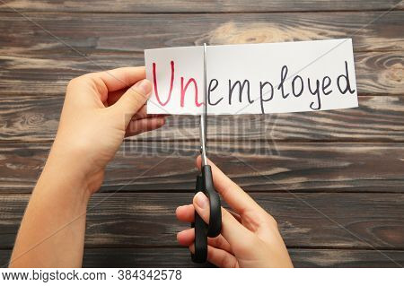 Scissors With Word Unemployed On Brown Background. Hand Holding Card With The Text Unemployed. Top V