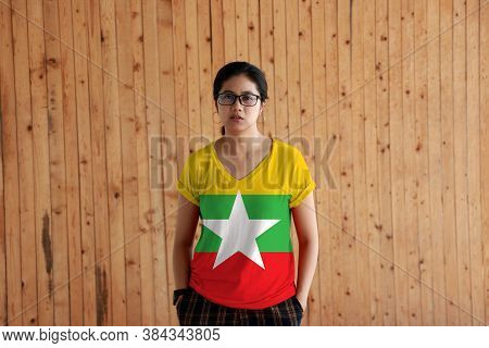 Woman Wearing Myanmar Flag Color Shirt And Standing With Two Hands In Pant Pockets On The Wooden Wal