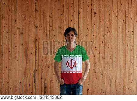 Man Wearing Iran Flag Color Shirt And Standing With Two Hands In Pant Pockets On The Wooden Wall Bac