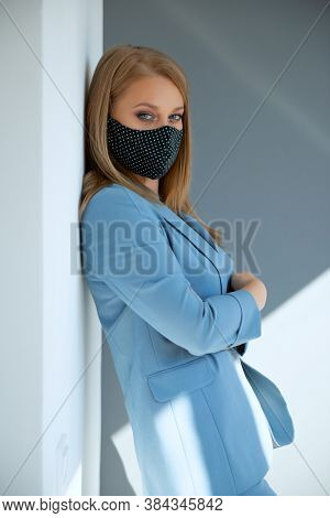 Beautiful mid adult blond woman wearing light blue suit in business style with protective mask during coronavirus epidemic and flu outbreak, indoor portrait, natural light. Virus or illness protection