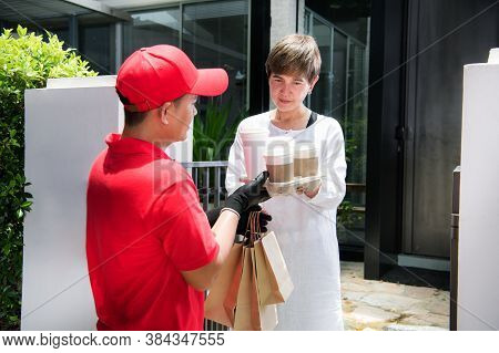 Asian Delivery Man In Red Uniform Delivering  Shopping Bags Of Food And Drink To Woman Recipient At