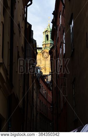The Steeple Tower Of A Church Visible High Above The Other Buildings In A Narrow Alley In Old Town O